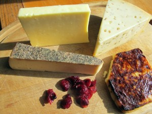 "Cheese is a source of pride among many Wisconsinites, nicknamed ""cheeseheads."" More than 600 varieties are made in the state, including, from upper left, aged cheddar, gouda with fennel, Juustoleipa cheese with jalapenos and Sartori Black Pepper BellaVitano. Dried cranberries represent another prominent Wisconsin offering. / Carol Guensburg"